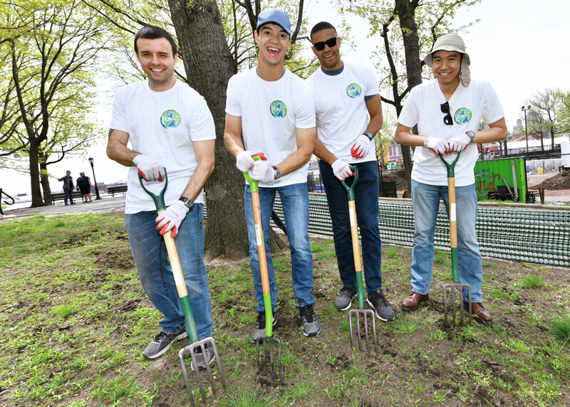 A group of people with garden rakes, working outside